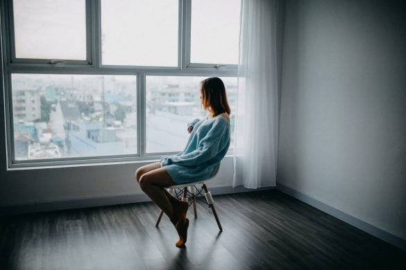 A girl sitting in her room in distress